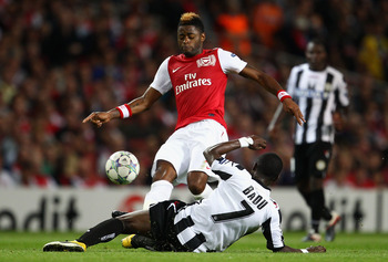 LONDON, ENGLAND - AUGUST 16:  Alex Song of Arsenal is tackled by Emmanuel Agyemang Badu of Udinese during the UEFA Champions League play-off first leg match between Arsenal and Udinese at the Emirates Stadium on August 16, 2011 in London, England.  (Photo