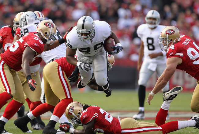 SAN FRANCISCO, CA - AUGUST 20:  Michael Bush #29 of the Oakland Raiders jumps over Seth Smith #26 of the San Francisco 49ers while running with the ball at Candlestick Park on August 20, 2011 in San Francisco, California.  (Photo by Ezra Shaw/Getty Images