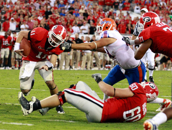 JACKSONVILLE, FL - OCTOBER 30:  Aaron Murray #11 of the Georgia Bulldogs runs past Justin Trattou #94 of the Florida Gators for a touchdown during the game at EverBank Field on October 30, 2010 in Jacksonville, Florida.  (Photo by Sam Greenwood/Getty Imag