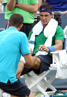 MASON, OH - AUGUST 19:  Rafael Nadal of Spain reacts has his foot looked after in between games in the second set against Mardy Fish during the Western & Southern Open at the Lindner Family Tennis Center on August 19, 2011 in Mason, Ohio.  (Photo by Elsa/