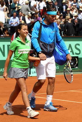PARIS, FRANCE - JUNE 05:  Rafael Nadal of Spain walks out onto the court escorted by a ball girl prior to the men's singles final match between Rafael Nadal of Spain and Roger Federer of Switzerland on day fifteen of the French Open at Roland Garros on Ju