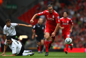 LIVERPOOL, ENGLAND - AUGUST 06:  Andy Carroll of Liverpool moves forward after a heavy challenge by Adil Rami of Valencia during the pre season friendly match between Liverpool and Valencia at Anfield on August 6, 2011 in Liverpool, England.  (Photo by Cl