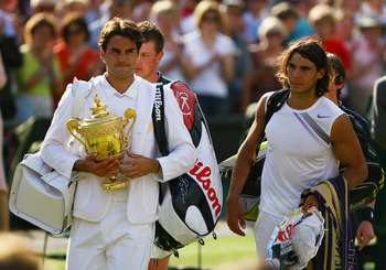 LONDON - JULY 08:  Roger Federer of Switzerland walks off court with the winners trophy alongside Rafael Nadal of Spain following the Men's Singles final match against  during day thirteen of the Wimbledon Lawn Tennis Championships at the All England Lawn
