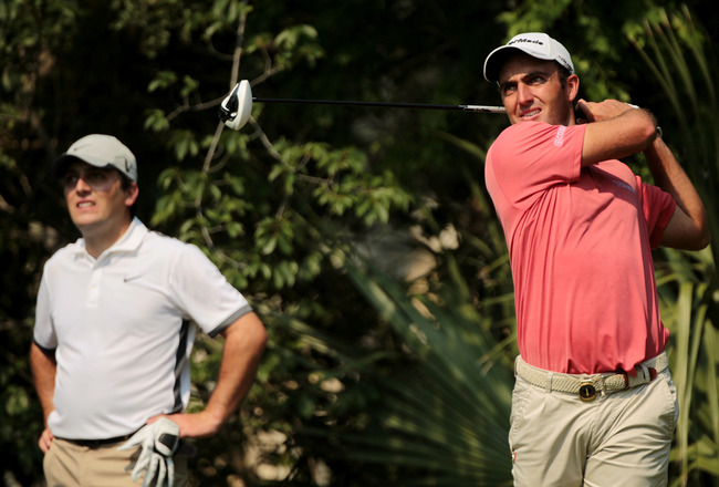 PONTE VEDRA BEACH, FL - MAY 10:  Edoardo Molinari of Italy (R) hits a shot while brother Fracesco Molinari looks on during a practice round prior to the start of THE PLAYERS Championship held at THE PLAYERS Stadium course at TPC Sawgrass on May 10, 2011 i