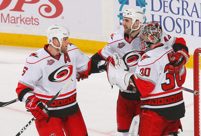 BUFFALO, NY - MARCH 15: Tim Gleason #6, Jay Harrison #44 and Cam Ward #30  of the Carolina Hurricanes celebrate after defeating the Buffalo Sabres  at HSBC Arena on March 15, 2011 in Buffalo, New York. Carolina won 1-0. (Photo by Rick Stewart/Getty Images
