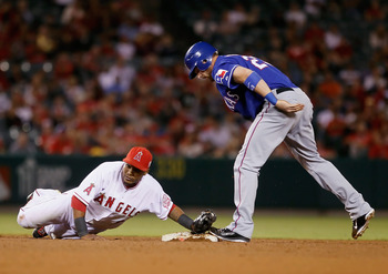ANAHEIM, CA - AUGUST 18:  Erick Aybar #2 of the Los Angeles Angels of Anaheim dives to tag the shoe of Craig Gentry #23 of the Texas Rangers who was safe at second with a stolen base in the ninth inning at Angel Stadium of Anaheim on August 18, 2011 in An