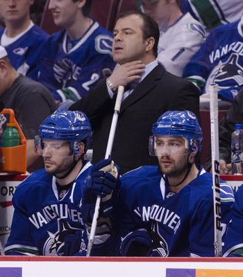VANCOUVER, CANADA - APRIL 21: Head coach Alain Vigneault of the Vancouver Canucks adjusts his shirt collar while Chris Higgins #20 (right) and Ryan Kesler #17 sit on the bench during the final minute of the third period in Game Five of the Western Confere