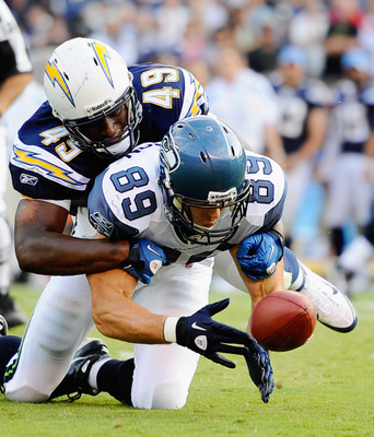 SAN DIEGO, CA - AUGUST 11: John Carlson #89 of the Seattle Seahawks drops the ball under pressure from Darryl Gamble #49 of the San Diego Chargers during the NFL preseason game at Qualcomm Stadium on August 11, 2011 in San Diego, California.  (Photo by Ke