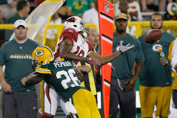 GREEN BAY, WI - AUGUST 19: Stephen Williams #18 of the Arizona Cardinals reaches for the football as he is hit by Charlie Peprah #26 of the Green Bay Packers in a preseason game at Lambeau Field on August 19, 2011 in Green Bay, Wisconsin. (Photo by Scott