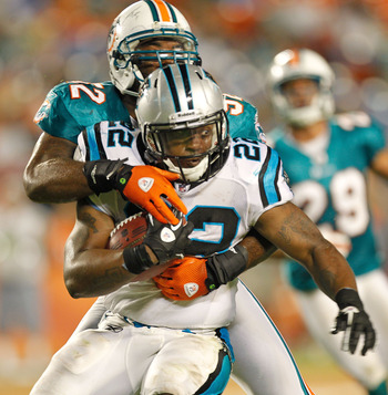 MIAMI GARDENS, FL - AUGUST 19: Tyrell Sutton #22 of the Carolina Panthers is tackled by Marvin Mitchell #52 of the Miami Dolphins during a preseason NFL game at Sun Life Stadium on August 19, 2011 in Miami Gardens, Florida.  (Photo by Mike Ehrmann/Getty I