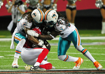 ATLANTA - AUGUST 12: Harry Douglas #83 of the Atlanta Falcons is tackled by Chris Clemons #30 and Nolan Carroll #28 of the Miami Dolphins during a preseason game at the Georgia Dome on August 12, 2011 in Atlanta, Georgia. (Photo by Scott Cunningham/Getty