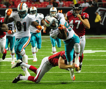 ATLANTA - AUGUST 12: Phillip Livas #85 of the Miami Dolphins breaks a tackle against Ken Parrish #6 of the Atlanta Flacons to score a touchdown on a punt return during a preseason game at the Georgia Dome on August 12, 2011 in Atlanta, Georgia. (Photo by