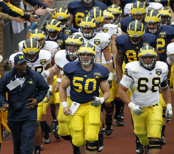ANN ARBOR, MI - APRIL 16:  David Molk #50 and Mike Martin #68 of the Michigan Wolverines lead their team onto the field prior to the start of the annual Spring Game at Michigan Stadium on April 16, 2011 in Ann Arbor, Michigan.  (Photo by Leon Halip/Getty
