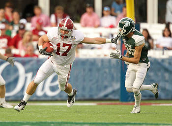 ORLANDO, FL - JANUARY 01: Brad Smelley #17 of the Alabama Crimson Tide runs after a catch stiffarming Josh Bodell #22 of the Michigan State Spartans during the Capitol One Bowl at the Florida Citrus Bowl on January 1, 2011 in Orlando, Florida.  (Photo by