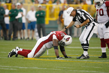 GREEN BAY, WI - AUGUST 19: Brandon Keith #72 of the Arizona Cardinals is attended to after an injury by Referee Jeff Triplette against the Green Bay Packers in a preseason game at Lambeau Field on August 19, 2011 in Green Bay, Wisconsin. (Photo by Scott B