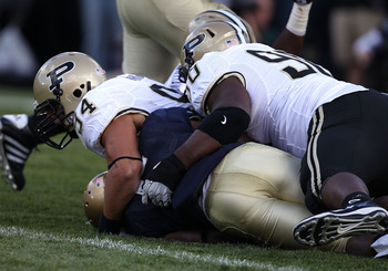 SOUTH BEND, IN - SEPTEMBER 04: Armando Allen Jr., #5 of the Notre Dame Fighting Irish is tackled in the end zone for a safety by Ryan Kerrigan #94 and Bruce Gaston #90 of the Purdue Boilermakers at Notre Dame Stadium on September 4, 2010 in South Bend, In