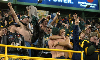 GREEN BAY, WI - DECEMBER 28: Fans of the Green Bay Packers celebrate after hearing the Minnesota Vikings were defeated by the Arizona Cardinals making the Packers the NFC North Division champions during a game against the Denver Broncos December 28, 2003