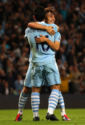 MANCHESTER, ENGLAND - AUGUST 15:  David Silva of Manchester City celebrates with Sergio Aguero after scoring the third goal during the Barclays Premier League match between Manchester City and Swansea City at Etihad Stadium on August 15, 2011 in Mancheste