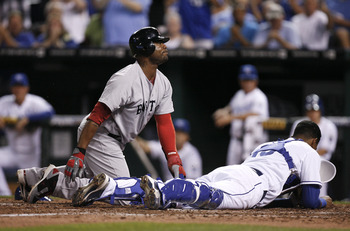 KANSAS CITY, MO - AUGUST 18:  Carl Crawford #13 of the Boston Red Sox reacts after being  tagged out at the plate by Salvador Perez #13 of the Kansas City Royals as he tries to score on Mike Aviles' pop fly in the fourth inning at Kauffman Stadium on Augu