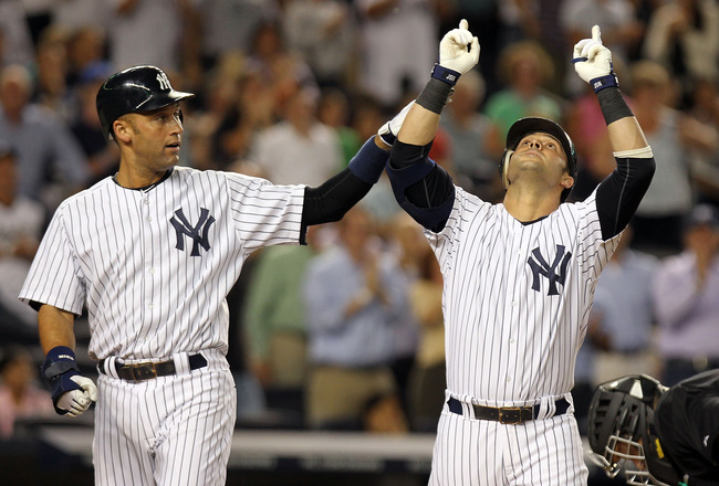 NEW YORK, NY - AUGUST 23:  Nick Swisher #33 of the New York Yankees is congratulated by teammate Derek Jeter #2 after his 3 RBI home run in the eighth inning against the Oakland Athletics on August 23, 2011 at Yankee Stadium in the Bronx borough of New Yo