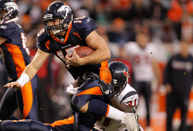 DENVER - DECEMBER 26:  Quarterback Tim Tebow #15 of the Denver Broncos is tackled by safety Bernard Pollard #31 of the Houston Texans during the fourth quarter at INVESCO Field at Mile High on December 26, 2010 in Denver, Colorado.  The Denver Broncos def