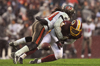 LANDOVER, MD - DECEMBER 12:  E.J. Biggers #31 of the Tampa Bay Buccaneers causes Graham Gano #4 of the Washington Redskins to fumble after a missed snap on an extra point attempt that would have tied the game with seconds remaining in the fourth quarter a