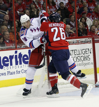 WASHINGTON, DC - APRIL 13:  Matt Hendricks #26 of the Washington Capitals hits Michael Sauer #38 of the New York Rangers in Game One of the Eastern Conference Quarterfinals during the 2011 NHL Stanley Cup Playoffs at Verizon Center on April 13, 2011 in Wa