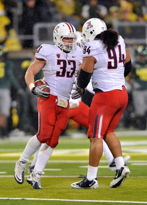 EUGENE, OR - NOVEMBER 26: Linebacker Jake Fischer #33 and nose tackle Lolomana Mikaele #94 of the Arizona Wildcats celebrate Fischer's fumble recovery the second  quarter of the game against the Oregon Ducks  at Autzen Stadium on November 26, 2010 in Euge