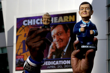 LOS ANGELES, CA - APRIL 20:  Fans hold up old souvenir figures of Los Angeles Lakers broadcaster Chick Hearn during unveiling ceremonies of a staute of Hearn before the Los Angeles Lakers and the Oklahoma City Thunder's  Game Two of the Western Conference