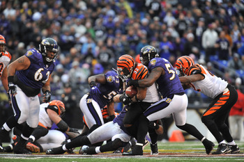 BALTIMORE, MD - JANUARY 2:  Cedric Benson #32 of the Cincinnati Bengals runs the ball while Ray Lewis #52 of the Baltimore Ravens makes a tackle at M&T Bank Stadium on January 2, 2011 in Baltimore, Maryland. The Ravens defeated the Bengals 13-6. (Photo by