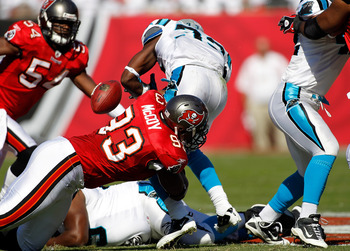 TAMPA, FL - NOVEMBER 14:  Defensive tackle Gerald McCoy #93 of the Tampa Bay Buccaneers causes running back Mike Goodson #33 of the Carolina Panthers to fumble during the game at Raymond James Stadium on November 14, 2010 in Tampa, Florida.  (Photo by J.