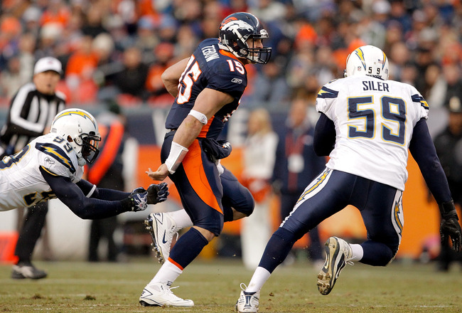 DENVER, CO - JANUARY 2:  Quarterback Tim Tebow #15 of the Denver Broncos eludes linebacker Kevin Burnett #99 and linebacker Brandon Siler #59 of the San Diego Chargers during the third quarter at INVESCO Field at Mile High on January 2, 2011 in Denver, Co