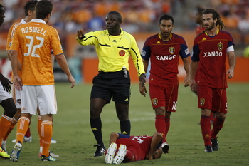 HOUSTON, TX - AUGUST 20: Referee Abiodun Okulaja separates Bobby Boswell #32 of the Houston Dynamo from Donny Toia #25 of Real Salt Lake as he lies on the ground at Robertson Stadium on August 20, 2011 in Houston, Texas.  (Photo by Eric Christian Smith/Ge