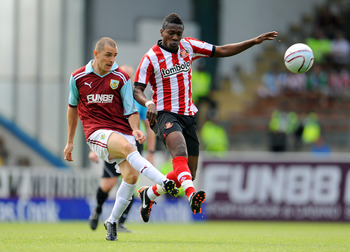 BURNLEY, UNITED KINGDOM - JULY 30: Asamoah Gyan of Sunderland (R) battles for the ball with Dean Marney of Burnley during the pre season friendly match between Burnley and Sunderland at Turf Moor on July 30, 2011 in Burnley, England. (Photo by Clint Hughe