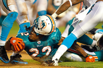 MIAMI GARDENS, FL - AUGUST 19:  Reggie Bush #22 of the Miami Dolphins loses his helmet during a Preseason NFL game against the Carolina Panthers at Sun Life Stadium on August 19, 2011 in Miami Gardens, Florida.  (Photo by Mike Ehrmann/Getty Images)