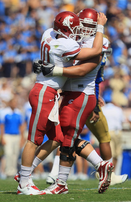 PASADENA, CA - OCTOBER 02:  Quarterback Jeff Tuel (L) #10 of the Washington State Cougars celebrates a touchdown with teammate B.J. Guerra #72 during the second quarter against the UCLA Bruins at the Rose Bowl on October 2, 2010 in Pasadena, California.