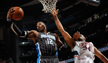 ATLANTA, GA - APRIL 24:  Dwight Howard #12 of the Orlando Magic grabs a rebound against Jason Collins #34 of the Atlanta Hawks during Game Four of the Eastern Conference Quarterfinals in the 2011 NBA Playoffs at Philips Arena on April 24, 2011 in Atlanta,