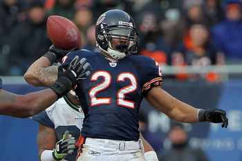 CHICAGO, IL - JANUARY 16:  Running back Matt Forte #22 of the Chicago Bears throws a pass over the arm of Kentwan Balmer #95 of the Seattle Seahawks as the pass is intercepted by Aaron Curry #59 in the second half of the 2011 NFC divisional playoff game a