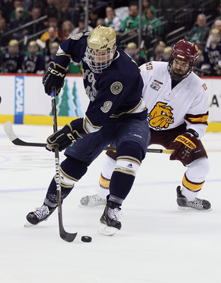ST. PAUL, MN - APRIL 07:  Anders Lee #9 of the Notre Dame Fighting Irish tries to keep the puck from Brady Lamb #2  of the Minnesota Duluth Bulldogs  during semifinals of the 2011 NCAA Men's Frozen Four on April 7, 2011 at the Xcel Energy Center in St. Pa