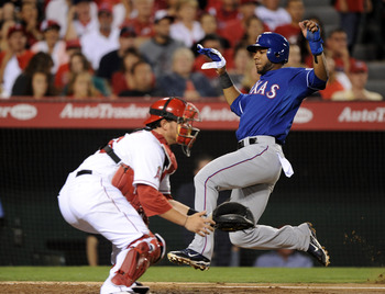 ANAHEIM, CA - AUGUST 15:  Elvis Andrus #1 of the Texas Rangers slides in ahead of a tag from Bobby Wilson #46 of the Los Angeles Angels of Anaheim during the fifth inning at Angel Stadium of Anaheim on August 15, 2011 in Anaheim, California.  (Photo by Ha