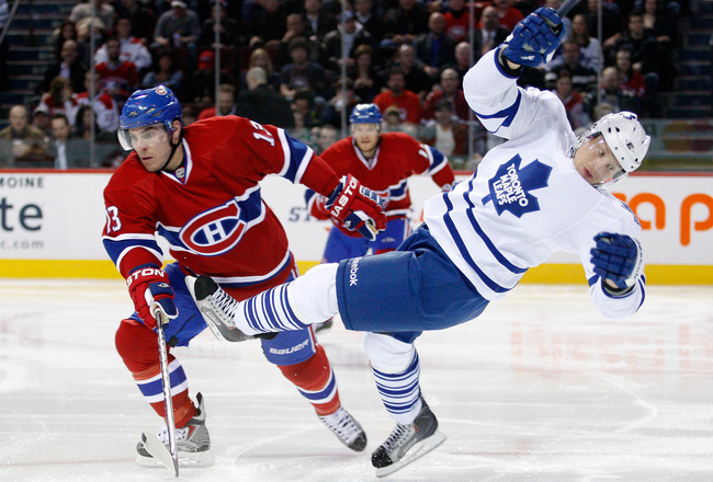 MONTREAL, CANADA - FEBRUARY 24:  Mike Cammalleri #13 of the Montreal Canadiens hauls down Mikhail Grabovski #84 of the Toronto Maple Leafs to the ice during the NHL game at the Bell Centre on February 24, 2011 in Montreal, Quebec, Canada.  The Maple Leafs