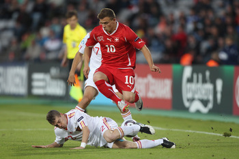 ARHUS, DENMARK - JUNE 25: Xherdan Shaqiri of Switzerland jumps over the challenge from Iker Muniain of Spain during the UEFA European Under-21 Championship Final match between Spain and Switzerland at the Arhus Stadium on June 25, 2011 in Arhus, Denmark.