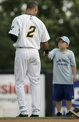 TRENTON, NJ - JULY 2: Derek Jeter of the New York Yankees shakes hands with a young boy after the national anthem during his minor league rehab start with the Trenton Thunder in a game against the Altoona Curve on July 2, 2011 at Mercer County Waterfront