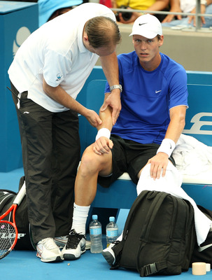 BRISBANE, AUSTRALIA - JANUARY 08:  Tomas Berdych of the Czech Republic receives attention for an arm injury in his quarter-final match against Thomaz Bellucci of Brazil during day six of the Brisbane International 2010 at Queensland Tennis Centre on Janua