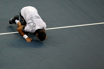 NEW YORK - SEPTEMBER 11:  Novak Djokovic of Serbia kisses the court after defeating Roger Federer of Switzerland to win his men's singles semifinal match on day thirteen of the 2010 U.S. Open at the USTA Billie Jean King National Tennis Center on Septembe
