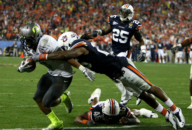 GLENDALE, AZ - JANUARY 10:  Running back LaMichael James #21 of the Oregon Ducks scores a touchdown on a two-yard touchdown reception as Mike McNeil #26 of the Auburn Tigers hit him in the endzone in the fourth quarter during the Tostitos BCS National Cha
