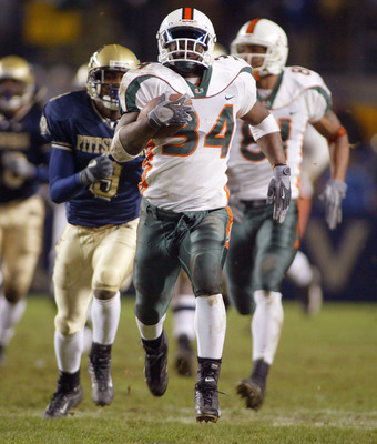 PITTSBURGH - NOVEMBER 29:  Jarrett Payton #34 of the Miami Hurricanes runs ahead of teammate Kellen Winslow #81 and Josh Lay #9 of the Pittsburgh Panthers  on November 29, 2003 at Heinz Field in Pittsburgh, Pennsylvania. Miami Won 28-14 and won the Big Ea