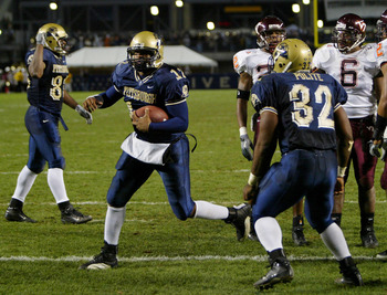 PITTSBURGH - NOVEMBER 8:  Quarterback Rod Rutherford #12 of the University of Pittsburgh Panthers escapes the Virginia Tech Hokies defense for a two yard touchdown to give the Panthers a 17-14 second quarter lead during NCAA football action on November 8,