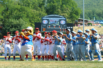 SOUTH WILLAMSPORT, PA - AUGUST 29:  Players from Japan and the United States Little League teams, dance with mascot Dugout before the game on August 29, 2010 in South Willamsport, Pennsylvania. Japan won the Little League World Series Championship 4-1.  (