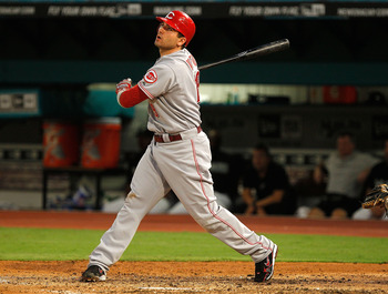 MIAMI GARDENS, FL - AUGUST 24:  Joey Votto #19 of the Cincinnati Reds hits a solo home run during game two of a doubleheader against the Florida Marlins at Sun Life Stadium on August 24, 2011 in Miami Gardens, Florida.  (Photo by Mike Ehrmann/Getty Images